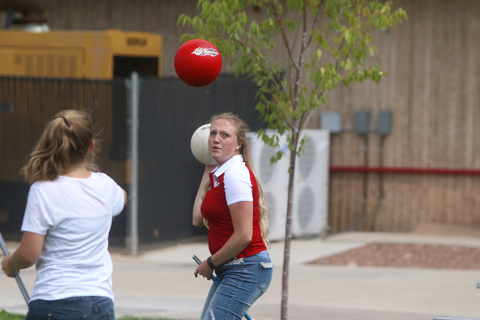 A woman prepares to throw a ball as a dodgeball flies toward her